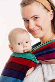 Model wearing baby in Lenny Lamb brand Lenny Hybrid half buckle meh dai carrier in print Carousel of Colors. A close up view showing top of the panel and arms from the side. Baby is sticking tongue out. Hood is removed for photo