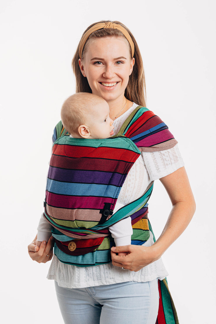 Model wearing baby in Lenny Lamb brand Lenny Hybrid half buckle meh dai carrier in print Carousel of Colors. A full view slightly sideways, model is smiling. Hood is removed for photo