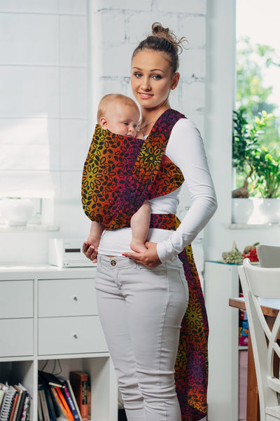 Mama & Roo's Lenny Lamb Exclusive, Sunset Wreath. Long woven wrap mock-up baby wrap. Wrap is gradient yellow, orange, red, and purple with a black weft visible on the reverse.