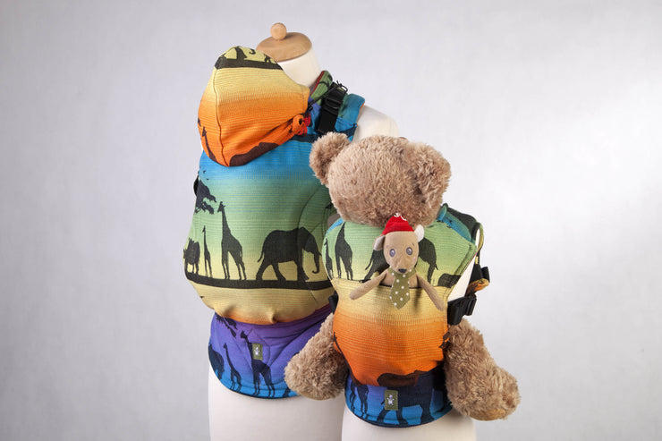 Lenny Lamb Rainbow Safari 2.0 Doll Carrier with pocket, holding teddy bear. Staged next to adult carrier in matching print