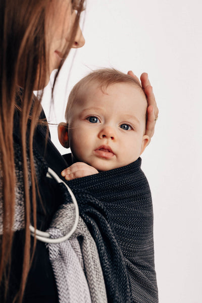 Close up of model carrying baby in Lenny Lamb brand ring sling in print Little Herringbone Ombre Grey