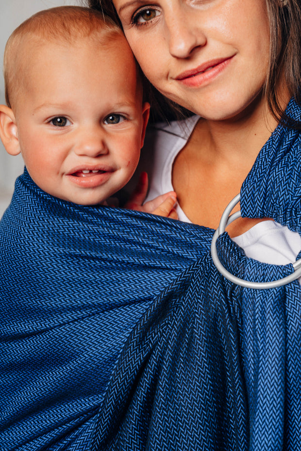 Model wearing baby in Lenny Lamb brand ring sling in herringbone print Cobalt. Close up of smiling baby