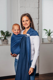 Model wearing baby in Lenny Lamb brand ring sling in herringbone print Cobalt.  Full view showing tail of sling