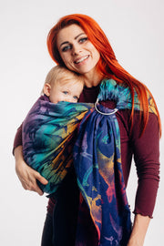 Model wearing baby in Lenny Lamb ring sling baby carrier in print Jurassic Park - New Era. Features Vibrant gradient background of purple to teal to yellow to red. Dark purple realistic-looking dinos and a on a dark purple weft. Leaning heads together and smiling