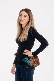 Model on a white background is wearing a Lenny Lamb fanny pack / waist bag, size large. It has 2 zippers and black webbing as the waist strap. The print is Wild Soul Daedalus. It is named after the mythical being. It has a black weft with feather images on a gradient background of bold yellow, red, and blue.