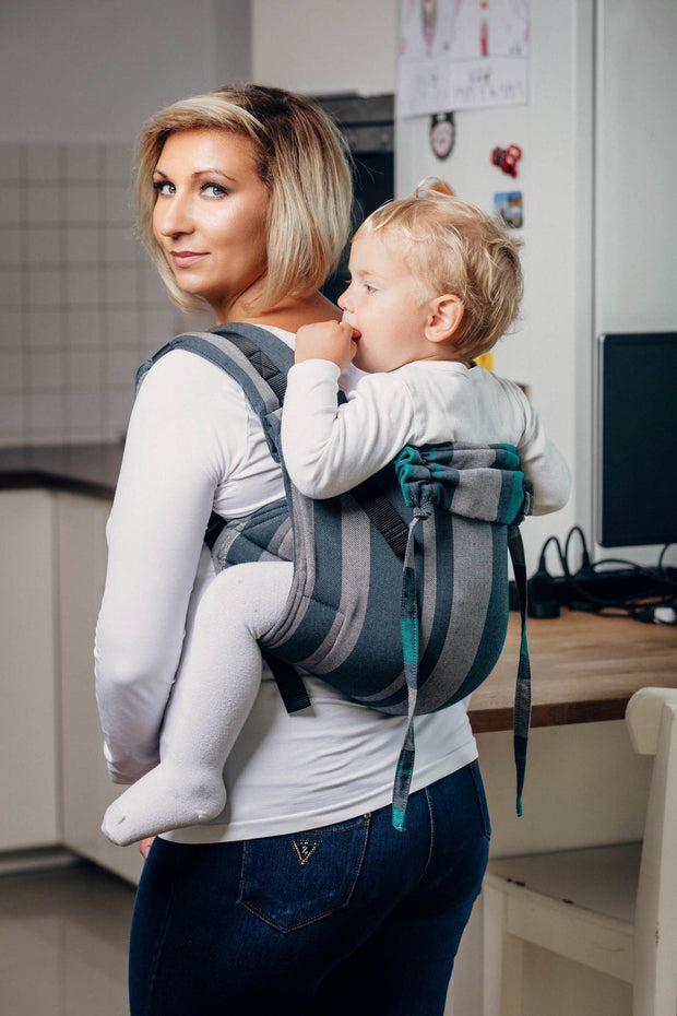 Woman wearing a child in a Lenny Lamb brand buckle onbuhimo baby carrier in print Smoky Mint. The print has vertical stripes in various shades of grey, accented with mint green stripes.