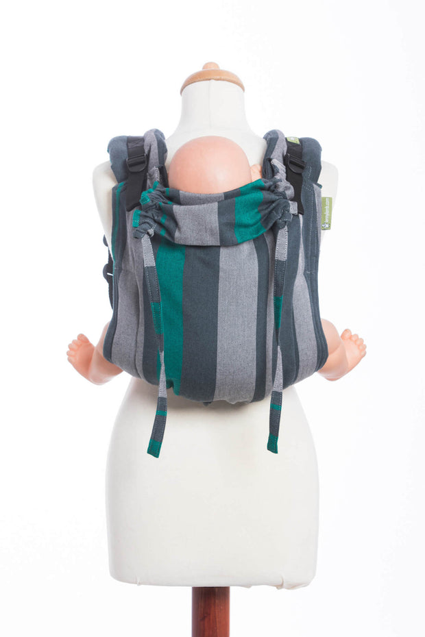 Mannequin wearing a doll in a Lenny Lamb brand buckle onbuhimo baby carrier in print Smoky Mint. The print has vertical stripes in various shades of grey, accented with mint green stripes.