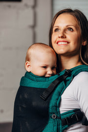 Woman carrying baby in a Lenny Lamb fully adjustable soft structured baby carrier (SSC). The print is Emerald Basic Line and is a stunning dark green herringbone weave.
