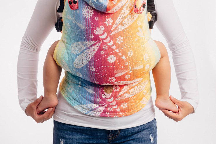 Woman wearing a child in a Lenny Lamb brand LennyGo ergonomic soft structured baby carrier (SSC) in print Dragonfly Rainbow. The print is a white weft with dragonflies on a gradient rainbow background.