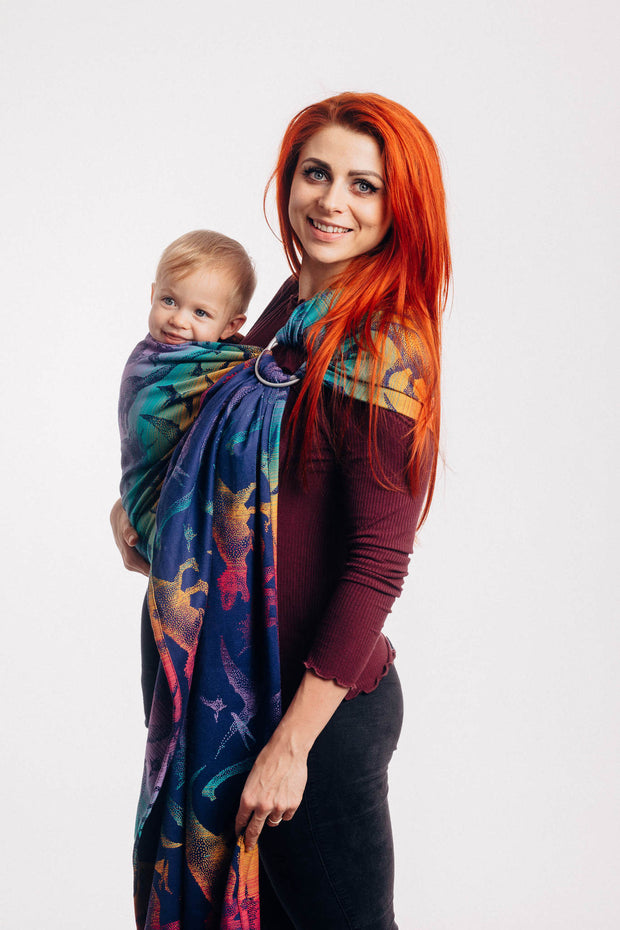 Model wearing baby in Lenny Lamb ring sling baby carrier in print Jurassic Park - New Era. Features Vibrant gradient background of purple to teal to yellow to red. Dark purple realistic-looking dinos and a on a dark purple weft. Side view