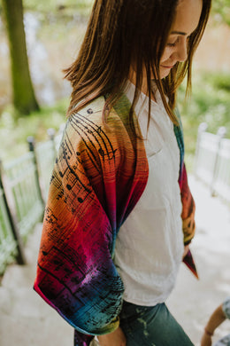 Woman wearing a Lenny Lamb shawl in print Symphony Rainbow Dark on stars overlooking a meadow. The print features clefs and music notes on a gradient rainbow with a dark weft.
