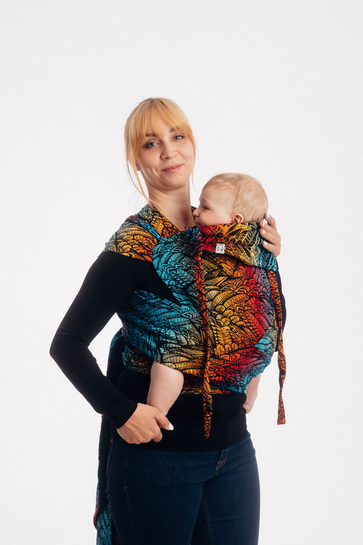 Woman carrying a baby in a Lenny Lamb meh dai / beh dai with wrap straps (wrap tai) in print Wild Soul Daedalus. The print has a black weft with feather pattern outlined in black on a background of electric blue, yellow, red, and orange.