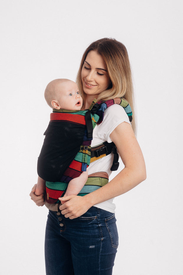 Brunette model is wearing a baby in a Lenny Lamb soft structured baby carrier (SSC or baby backpack) in print Carousel of Colors. This cotton baby carrier has thick horizontal stripes in shades of green, turquoise, red, purple, blue, magenta, and pink with thin black stripes in-between the colors. This is the mesh version with has a black mesh panel instead of the front fabric panel for wearing in hot climates.