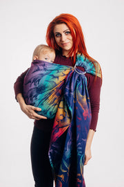 Model wearing baby in Lenny Lamb ring sling baby carrier in print Jurassic Park - New Era. Features Vibrant gradient background of purple to teal to yellow to red. Dark purple realistic-looking dinos and a on a dark purple weft. Standing