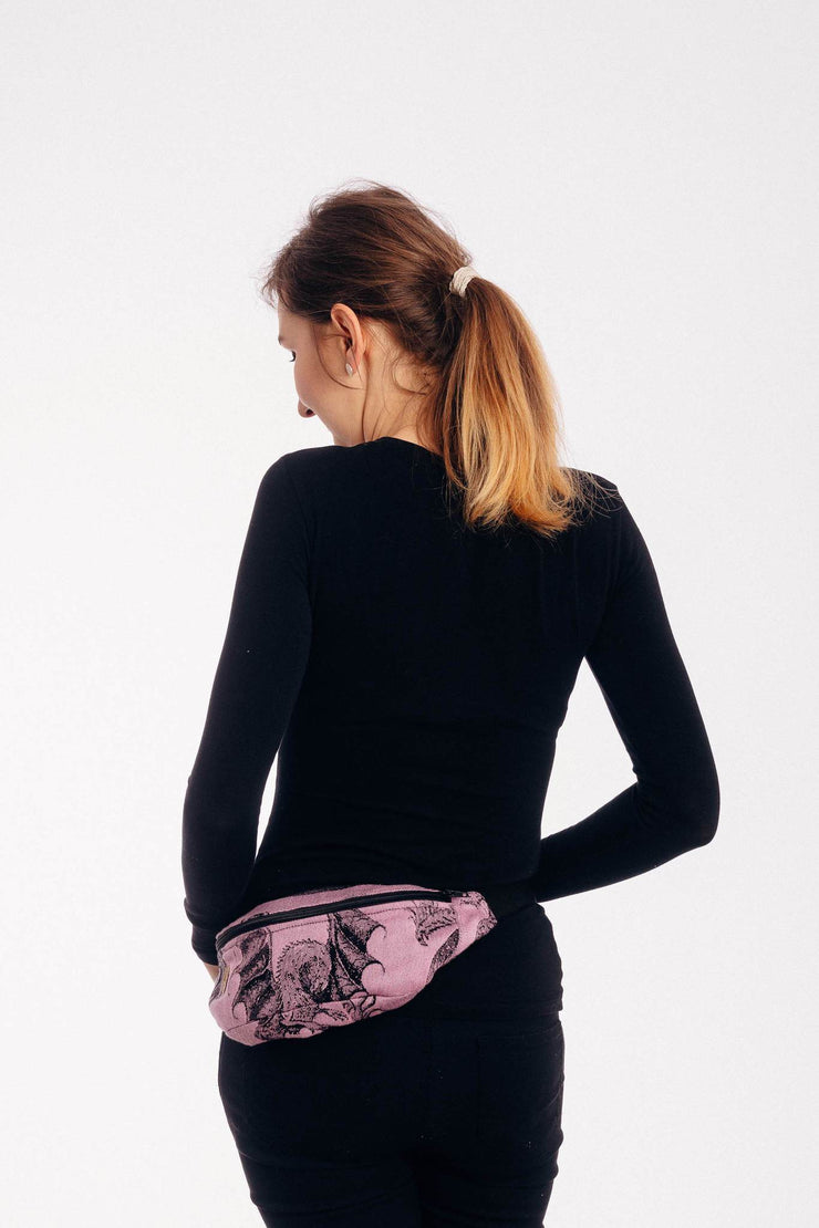 Representative photo. Model is dressed in black on a white background wearing Lenny Lamb brand fanny pack in the small / mini size in print Dragon - Dragon Fruit. The bag has one zipper. The print is a black weft with realistic-looking dragons on a pink background.