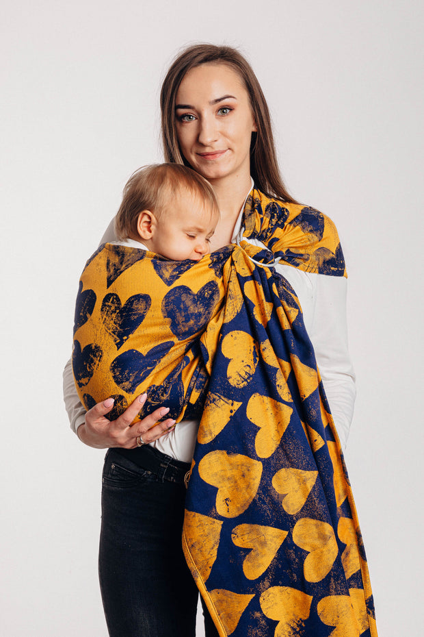 Lenny Lamb ring sling, Lovka Mustard and Navy Blue. Silver rings with navy blue hearts on a yellow background and blue weft. Full body, showing off the reverse