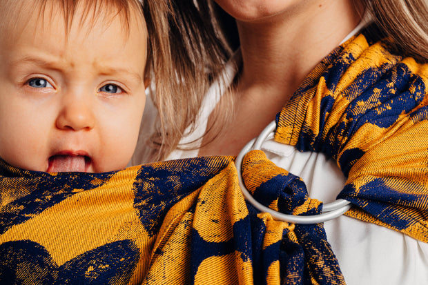 Lenny Lamb ring sling, Lovka Mustard and Navy Blue. Silver rings with navy blue hearts on a yellow background and blue weft. Close up.