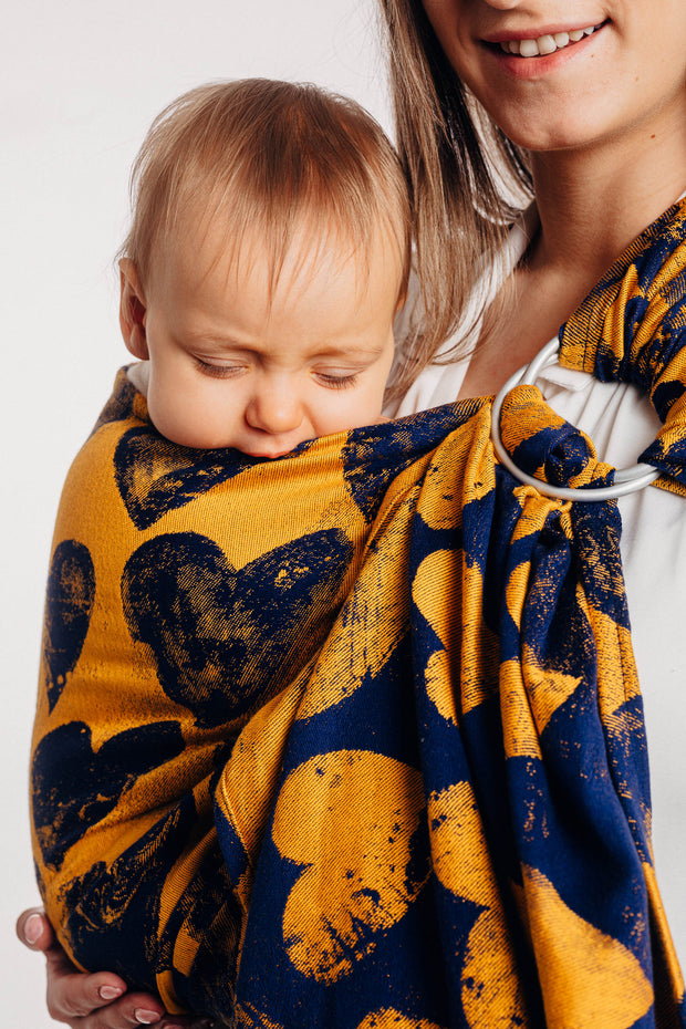 Lenny Lamb ring sling, Lovka Mustard and Navy Blue. Silver rings with navy blue hearts on a yellow background and blue weft. Side view, little one chewing on top of sling