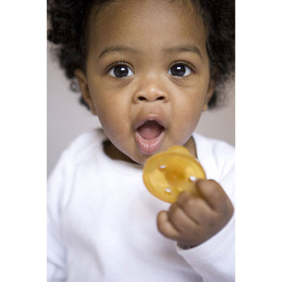 Baby holding Natursutten round rubber Original pacifier. Made in Italy.