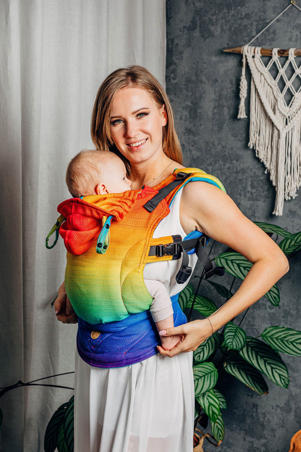 angled, smiling. Lenny Lamb brand soft structured baby carrier (SSC) the LennyGo in print Rainbow Baby