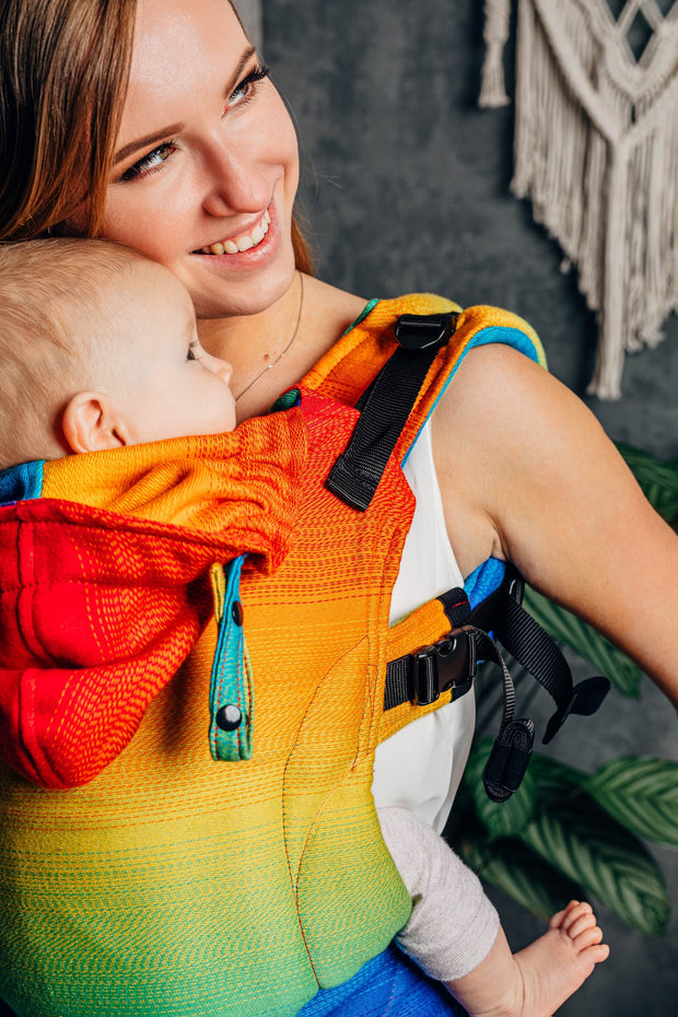 closeup, looking to the side. Lenny Lamb brand soft structured baby carrier (SSC) the LennyGo in print Rainbow Baby