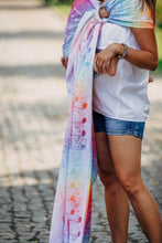 Load image into Gallery viewer, Woman wearing a child in a Lenny Lamb ring sling for babywearing in print Symphony Rainbow Light. The print has clefs and music notes in white (white weft) on a gradient rainbow background. The rainbow is vibrant.