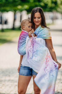 Woman wearing a child in a Lenny Lamb ring sling for babywearing in print Symphony Rainbow Light. The print has clefs and music notes in white (white weft) on a gradient rainbow background. The rainbow is vibrant.