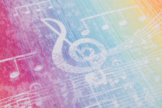 Close up of the fabric of a Lenny Lamb long woven wrap for babywearing in print Symphony Rainbow Light. The print has clefs and music notes in white (white weft) on a gradient rainbow background. The rainbow is vibrant.