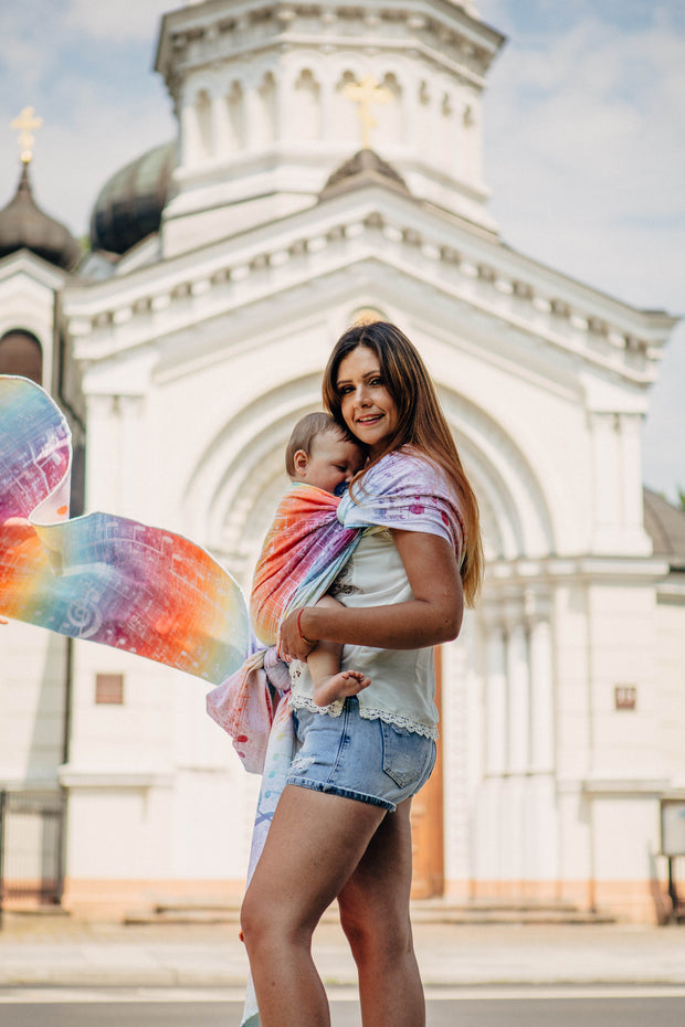 Woman wearing a child in a Lenny Lamb long woven wrap for babywearing in print Symphony Rainbow Light. The print has clefs and music notes in white (white weft) on a gradient rainbow background. The rainbow is vibrant.