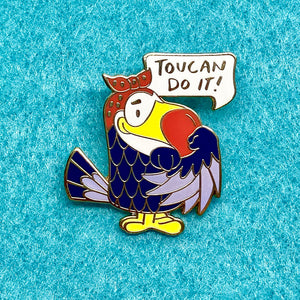 "Tootie Toucan doing her best Rosie the Riveter in this positive, inspiring hard enamel pin. ""Toucan Do It!"", 1.25 inches tall, vibrant colors, and gold plating. You Can Do It. We Can Do It. Valentine's Day gift, Romance, Romantic gift, friendship, positive affirmation, inspirational message, woodlawn animals, kawaii cute, Toucan Sam, Fruit Loops"