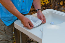 Man demonstrating how to use the refuse hole with easy-snap locking system to easily hold a trash bag in place.