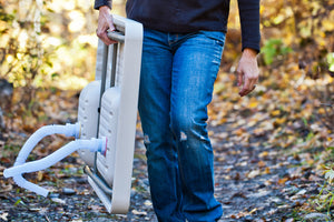 Woman demonstrating the simple portability of the Ultimate Outdoor Work Station.