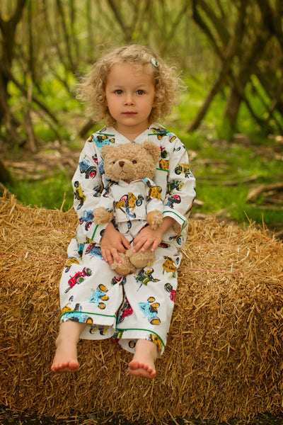 little girl wearing tractor pyjamas and holding teddy dressed in matching tractor pyjamas