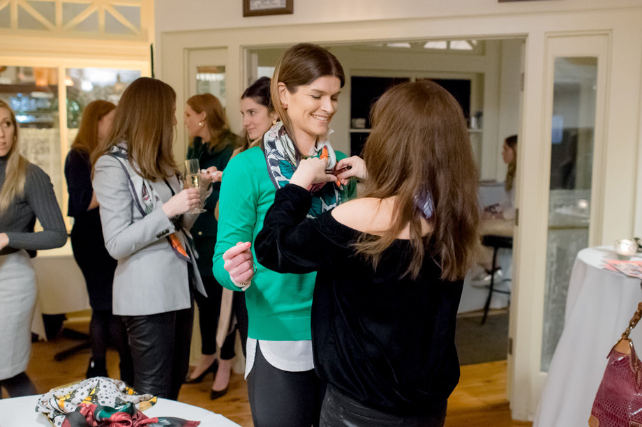 An attendee at the DESEDA Ladies Night Out event styling a silk scarf on her friend's neck.