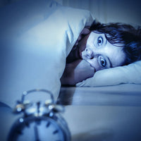 Woman stares at alarm clock ADD sleep
