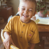 Smiling boy wearing a mustard retro kids tee with embroidered Vegemite logo by kids clothing brand My Brother John