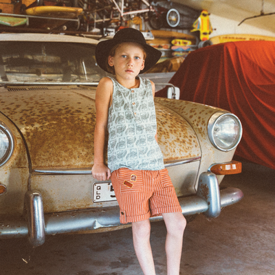 Boys fashion model on rusty retro car wearing My Brother John Mighty Vegemite Muscle Tank, Oxley Safari Shorts. Vintage childhood boys fashion.