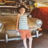 Boy leaning on old car wearing black hat and muscle tank MBJ shorts