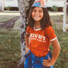 Girl with brown hair and a cheesy grin. She is wearing a retro kids t-shirt and girls suspender skirt standing in front of a tree