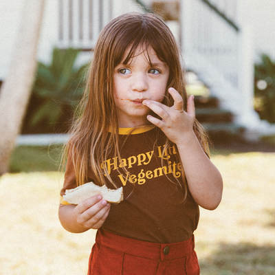 Little girl eating a Vegemite sandwich wearing a Happy little vegemite girls retro T-shirt. Designed by kids clothing brand Lacey Lane