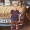 Cute boy sitting on vintage car wearing retro ringer tee and trousers from Vegemite collection