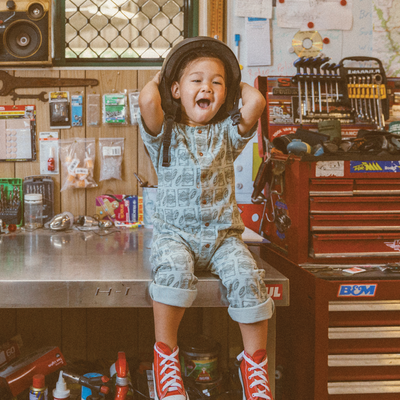 Little boy sitting on work bench wearing a helmet. His clothes are a Vegemite print romper by My Brother John