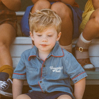 Little blonde boy sitting on stairs wearing a boys retro shirt. Boys button up shirt by My Brother John