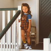 Little girl standing on stairs in blue t-shirt and overalls, a steel blue retro t-shirt with cream trims paired with lacey lane Jamie overalls