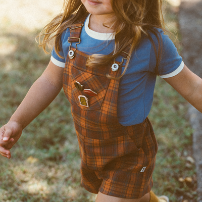 Little girl walking wearing true tee, a steel blue t-shirt with cream trims paired with lacey lane Jamie overalls