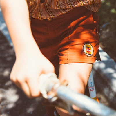 Close up picture of retro orange corduroy shorts by Lacey Lane. Featuring an embroidered vegemite patch on the leg.
