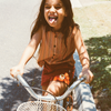 Girl poking out her tongue riding a vintage bike. Girls is wearing a striped retro kids blouse and girls retro corduroy shorts by Lacey Lane