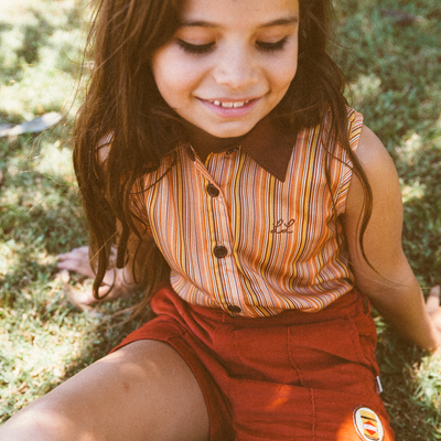 Girl sitting on the grass with long brown hair wearing a kids retro blouse by Lacey Lane and kids retro shorts in burnt orange.