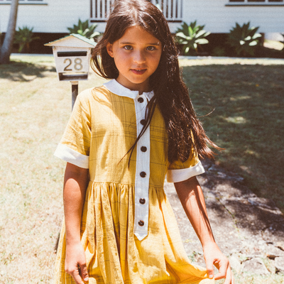Retro girl with long brown hair wearing a yellow and white retro dress by Lacey Lane