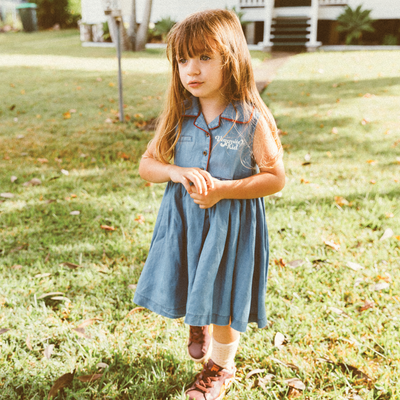 Little girl with long brown hair wearing a denim blue retro dress. Vegemite dress by Lacey Lane